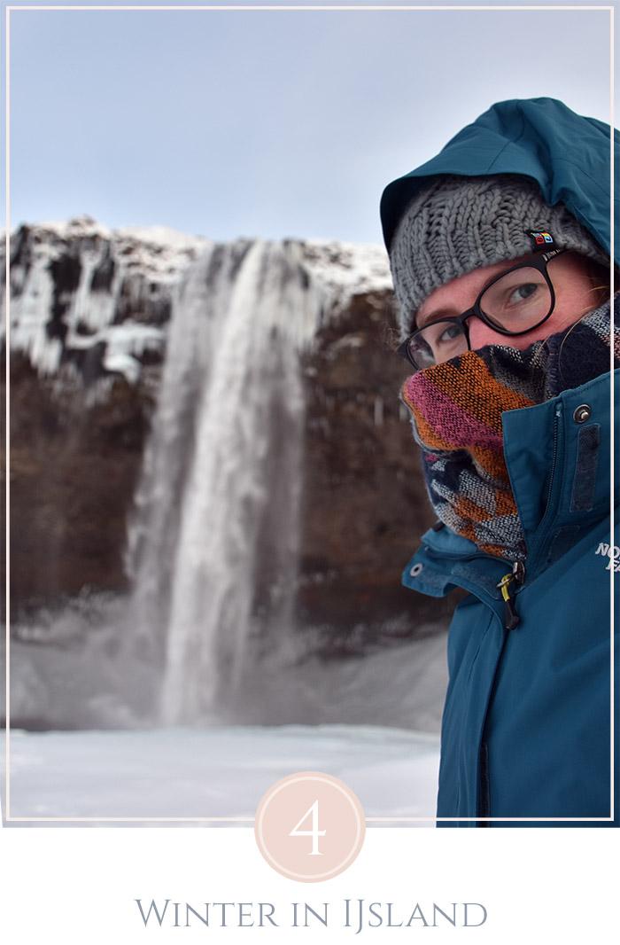 Een selfie in warme kleding ingepakt voor een waterval in IJsland met sneeuw op de grond