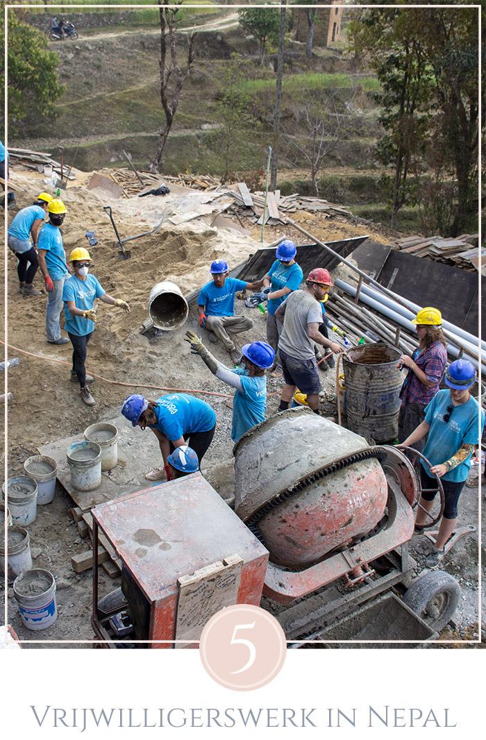 Een groep mensen met blauwe t-shirts van All Hands Volunteers werkt hard om een school te bouwen in Nepal, cement wordt gemengd in de molen en verdeeld