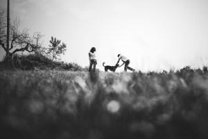 pareja juega en el campo con labrador negro