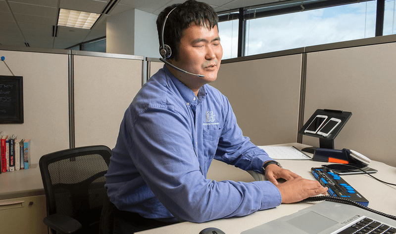 A worker with a visual impairment uses accessible technology on the job.