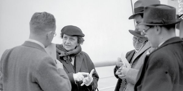 Black and white photo of Secretary of Labor Frances Perkins, the first woman in the U.S. Cabinet, addressing members of the press.