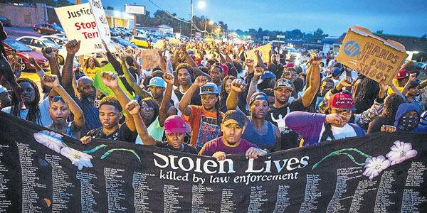 Decenas de afroamericanos protestaban en Misuri, mostrando una pancarta con los nombres de víctimas de agentes policiales en Estados Unidos.