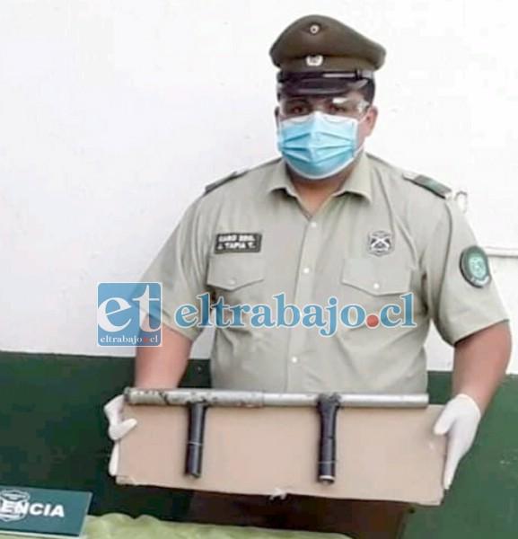 Un funcionario de Carabineros muestra la escopeta hechiza que utilizó el delincuente para disparar contra los uniformados.