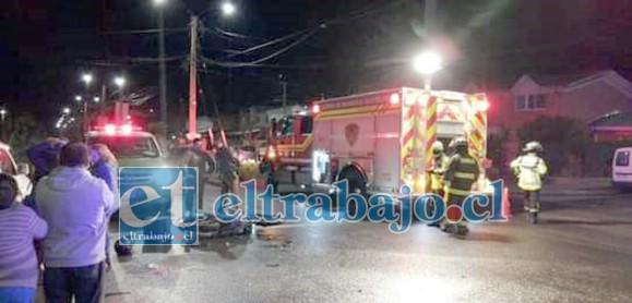 Carabineros y personal del SAMU en el lugar de los hechos, junto a la motocicleta que aparece tirada en el suelo tras el accidente.