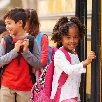 Girl smiling as she boards a school bus