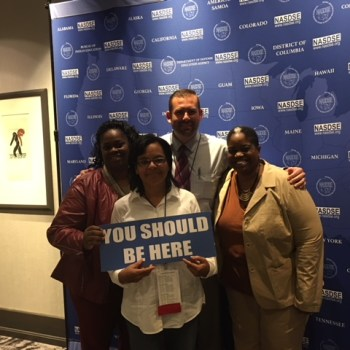 "Chad Gundry with group of NASDE conference attendees with the sign ""You Should Be Here"""