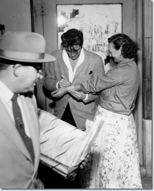 An unidentified woman approached Elvis Presley at Goodfellows headquarters Dec. 16, 1957, with a request: 'Elvis, please autograph my arm!'.