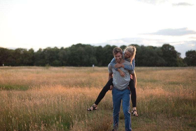 engagement shoot london laughing couple piggy back