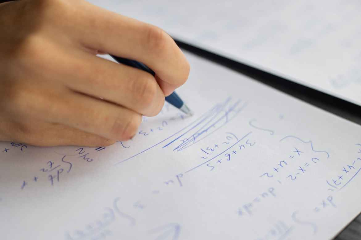 crop person solving equations on paper