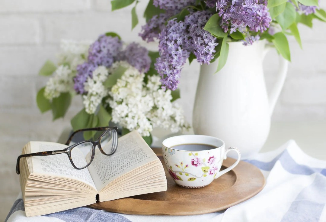 Coffee a book and vase of flowers