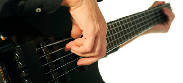 detail of the musician and his instrument while playing electric bass guitar