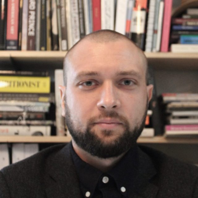 Daniel Atkinson sitting in front of a bookshelf with a neutral expression. He has a beard and is wearing a black button-up shirt.
