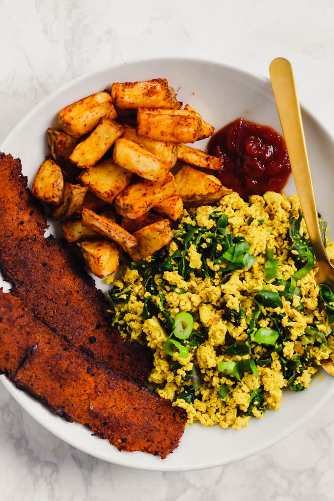 This loaded Vegan Breakfast Plate is the ultimate weekend brunch! It features eggy tofu scramble, veggie bacon, and crispy roasted potatoes.