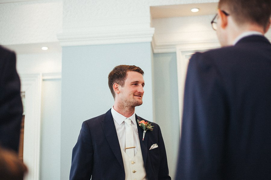 The groom wearing a blue suit and white tie