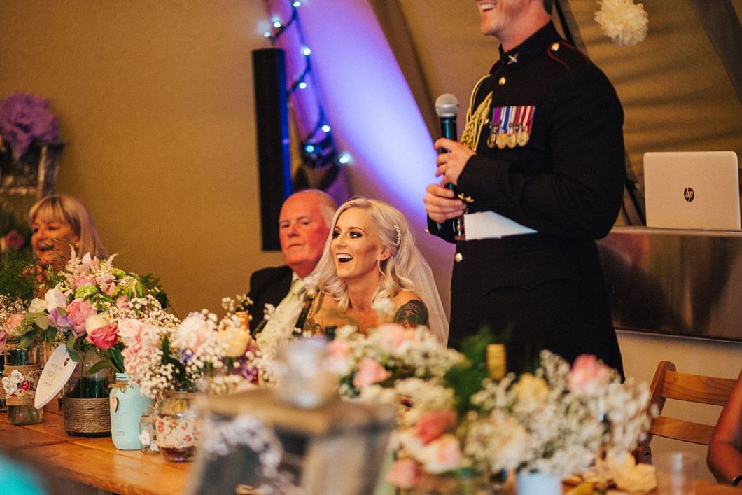 Tattooed bride laughing during speeches