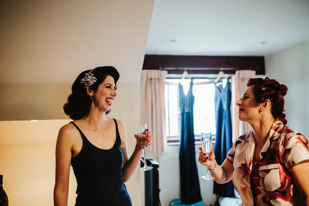 Bride and bridesmaid laughing with champagne
