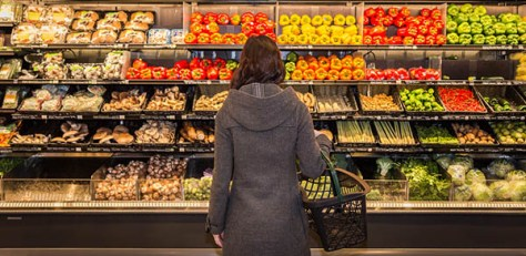 woman with basket facing produce aisle