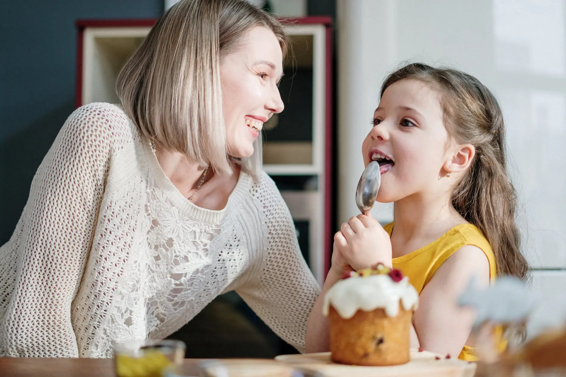 woman in white knit sweater smiling while little girl licking icing on her spoon