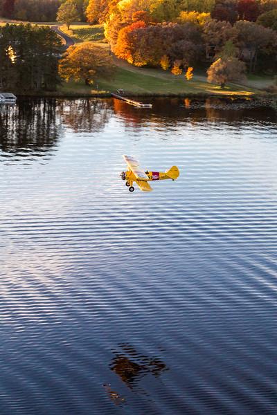 A Boeing Stearman cruises low over a Minnesota lake on a beautiful fall evening.