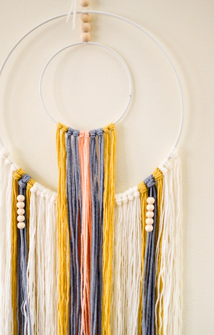 Attaching second row of yarn and more wooden beads to DIY wall hanging