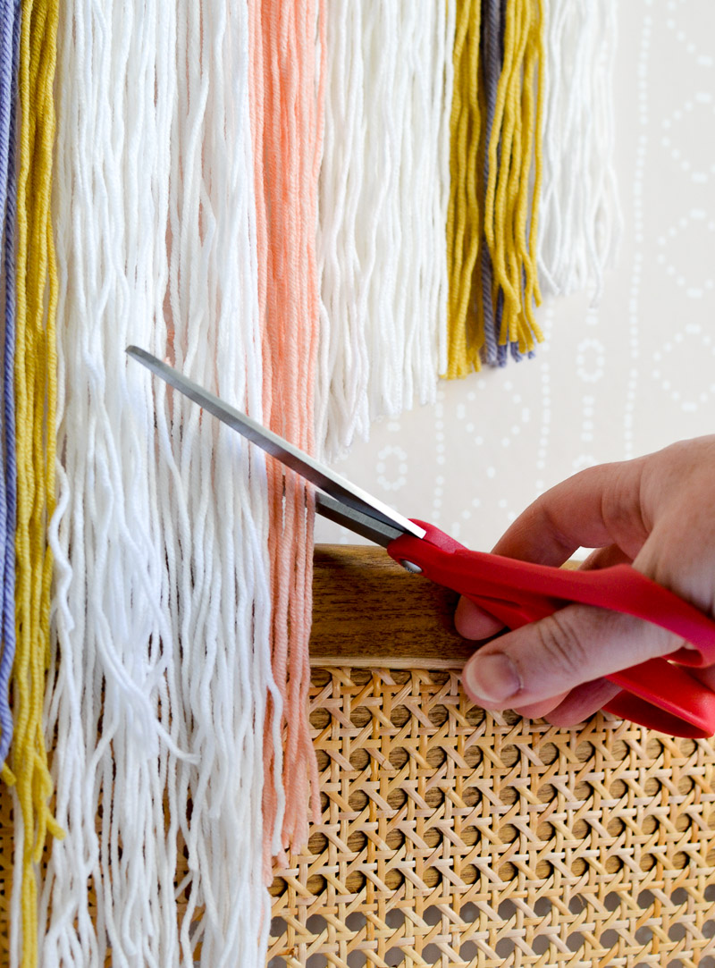 Trimming yarn with scissors on DIY wall hanging