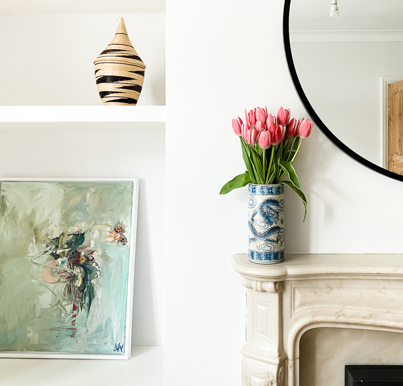 Tulips and abstract art by marble fireplace