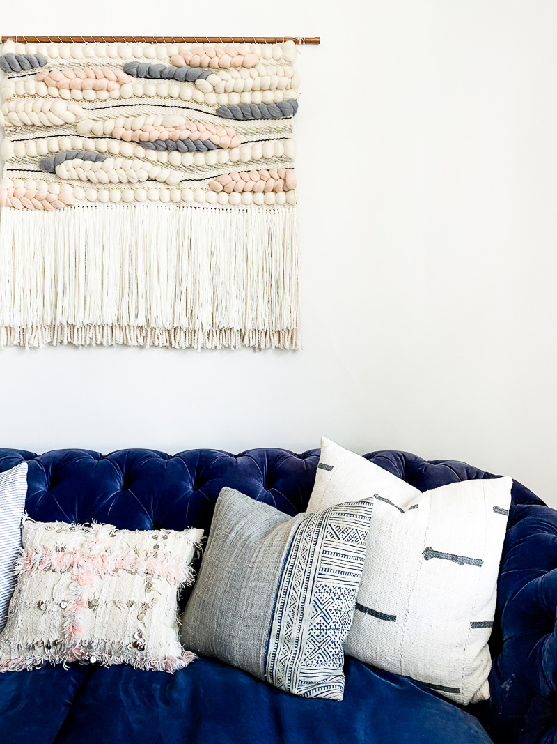 Moroccan, hmong & mudcloth cushions on navy chesterfield with woven tapestry