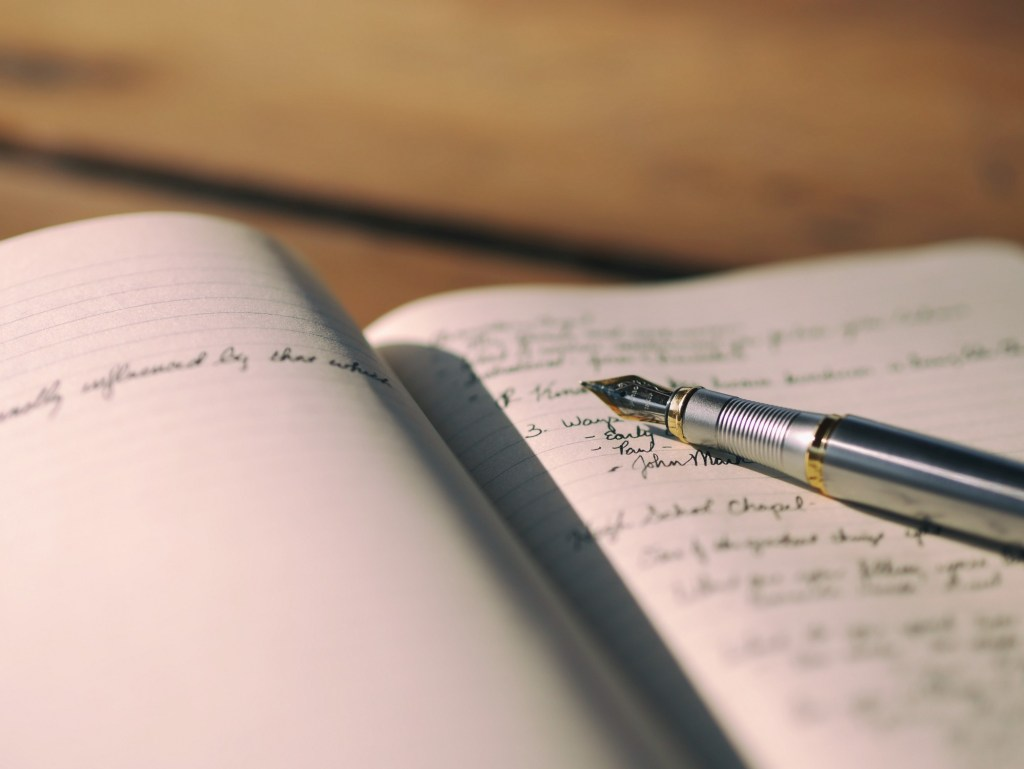 Pen rests on a journal.