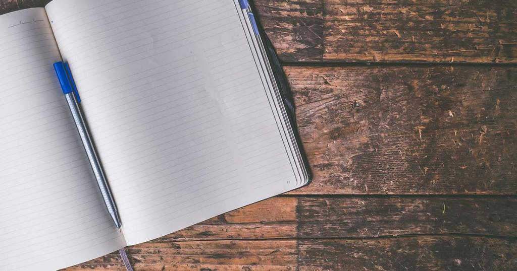 An empty notebook lies on a table, open, with a pen in the crease.