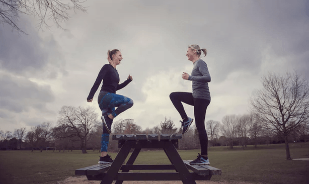 Two women do their balancing exercise together in the park.
