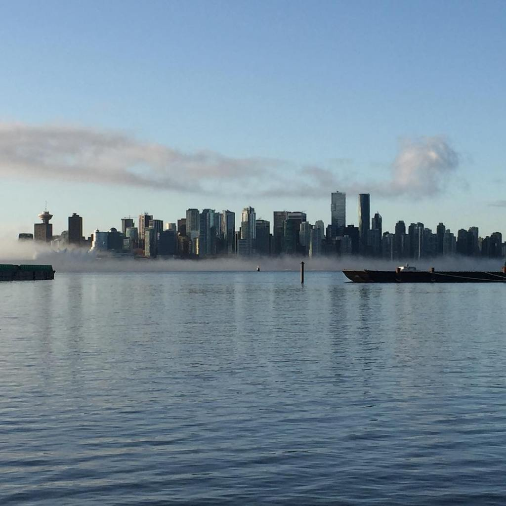 Looking across the calm ocean to downtown vancouver. The sky is blue and there is a low fog cloud along the line where downtown meets to ocean on the otherside.