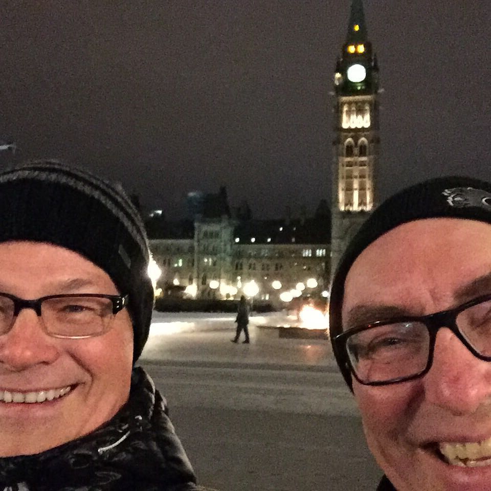 A close up of two mens' smiling faces. Both are wearing black toques and glasses. The parliament buildings in Ottawa with their high clocktower are in the background. The sky is black.