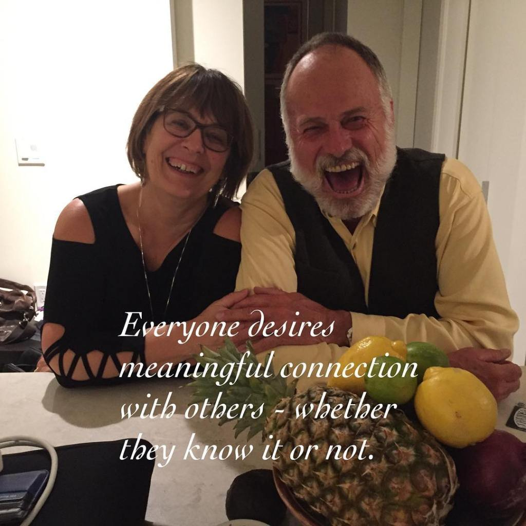 """A man and a woman standing behind a white shiny counter with a bright window being them. They are shoulder to shoulder and smiling really widely with his left hand reaching across to hold her right hand. He is on the right and in a yellow dress shirt with a black vest. She is on the left and wearing a black shirt. There is a fruit bowl with a pineapple and lemons in the foreground on the right. Text put over top on the bottom half of the image is white and reads """"Everyone desires meaningful connection with others - whether they know it or not!"""""""