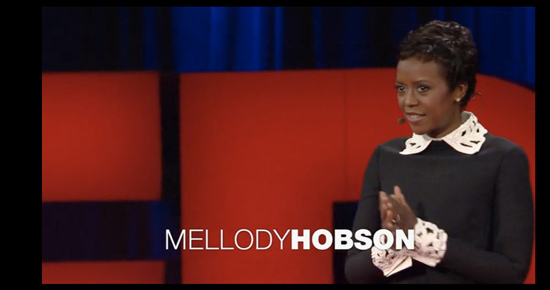 Mellody Hobson stand on stage delivering her talk at a TED conference