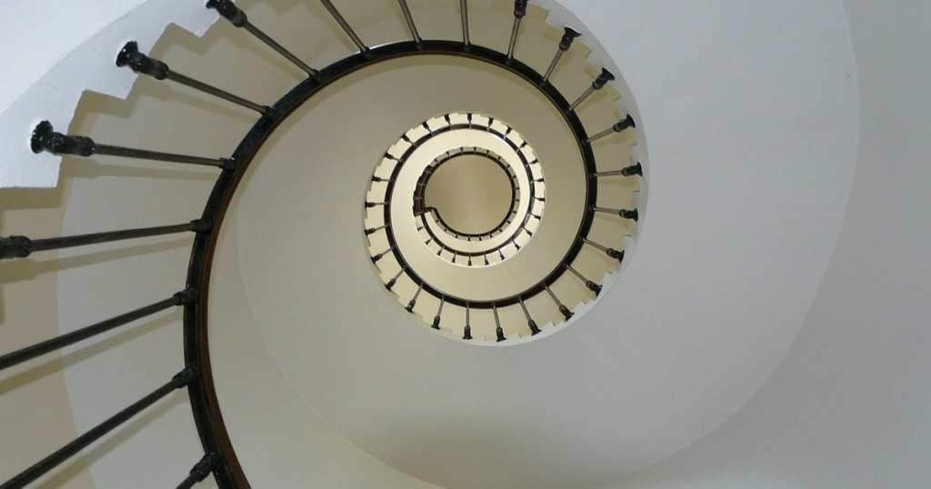 A winding staircase goes up and up into the light.