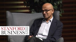 Satya Nadella sits on stage at the Stanford School of Business talking about empathy.