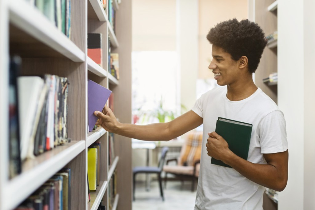 A Black student reviews books in the campus library.