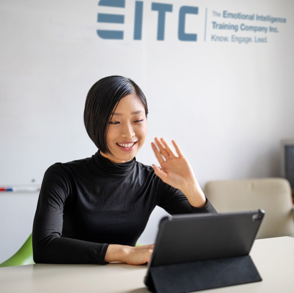 An EQ-i 2.0 certified coach and human resources professional waves hello into the computer, with an EITC logo in the background.