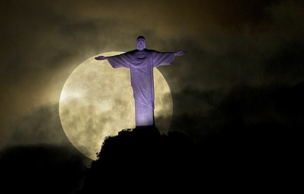 """A """"supermoon"""" is seen behind the Christ the Redeemer statue in Rio de Janeiro, Sunday, May 6, 2012. A supermoon is the coincidence of a full moon (or a new moon) with the closest approach the moon makes to the Earth. (AP Photo/Victor R. Caivano)"""
