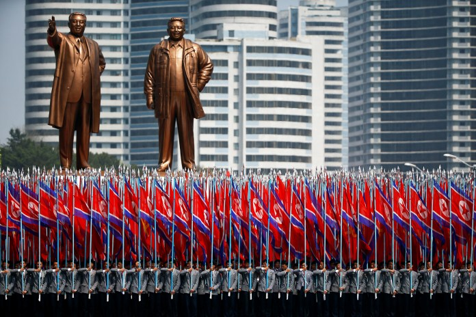 """People carry flags in front of statues of North Korea founder Kim Il Sung (L) and late leader Kim Jong Il during a military parade marking the 105th birth anniversary Kim Il Sung, in Pyongyang April 15, 2017. The men carrying flags are wearing North Korean university uniforms. The float containing the statues is often marks the start of a section of the parade led by people chosen to represent ordinary citizens, as opposed to soldiers or military equipment. Once the parade is over, and the float has completed its official function, a large white sheet is placed over each statue in order to preserve the """"Supreme Dignity"""" of each figure as the float meanders its way back through the city amid normal traffic. REUTERS/Damir Sagolj SEARCH """"PARADE WID"""" FOR THIS STORY. SEARCH """"WIDER IMAGE"""" FOR ALL STORIES. - RTS12G64"""