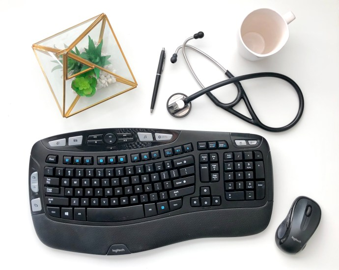 physician assistant desk with keyboard stethoscope and coffee cup