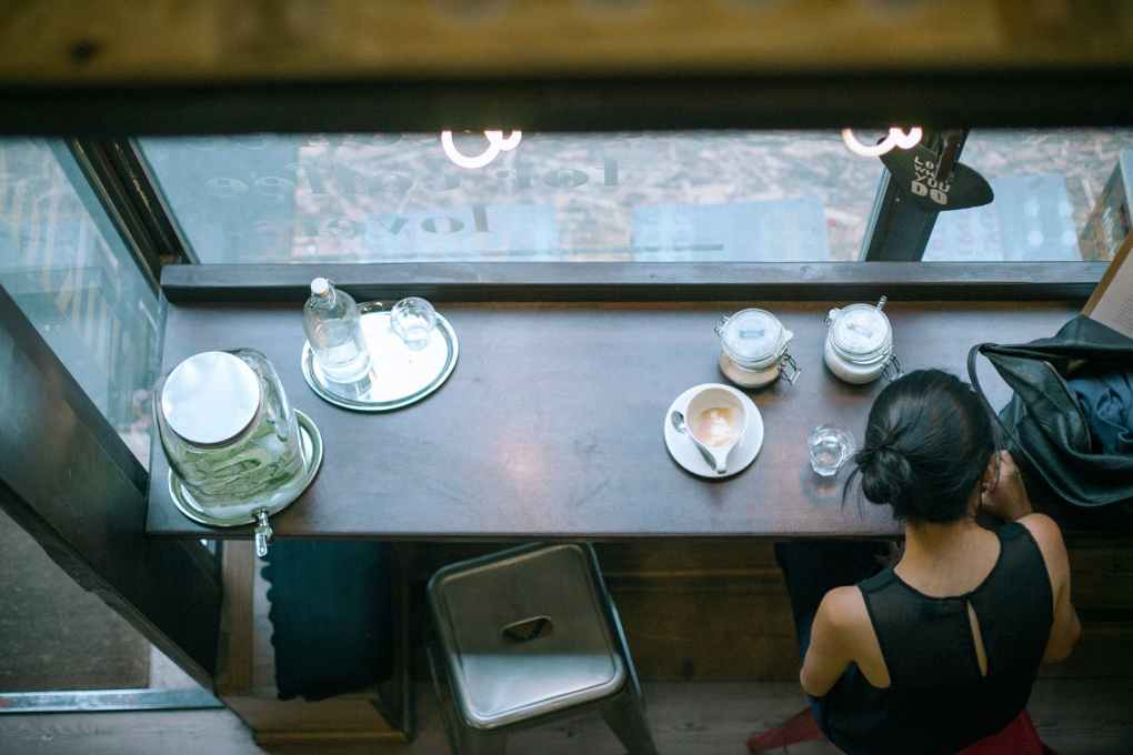 unrecognizable female sitting in cafe with coffee