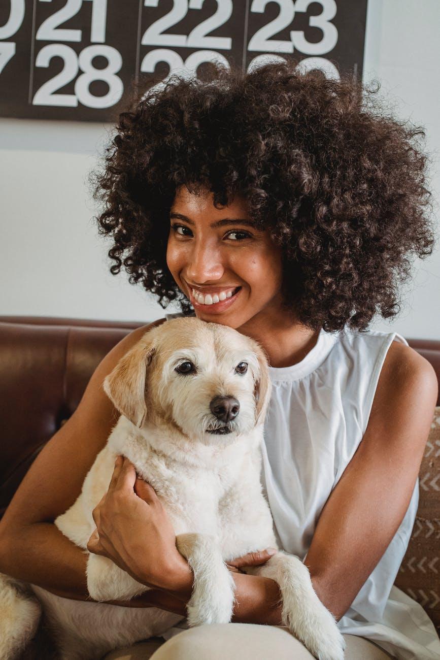 smiling black owner embracing pet on sofa at home