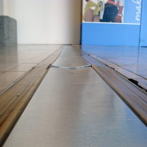 The rolling motion of high-point-load, small wheeled traffic can quickly cup under-designed coverplate systems as well as caused damage to adjacent flooring.