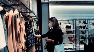 A woman with a mask checking out some clothing at a Soho store.