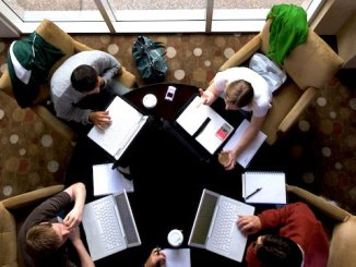 Photo of four people having a meeting around a roundtable