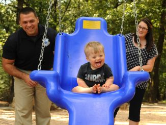 Photo of a family with baby on a blue swing, and father in the back left and mother in the back right