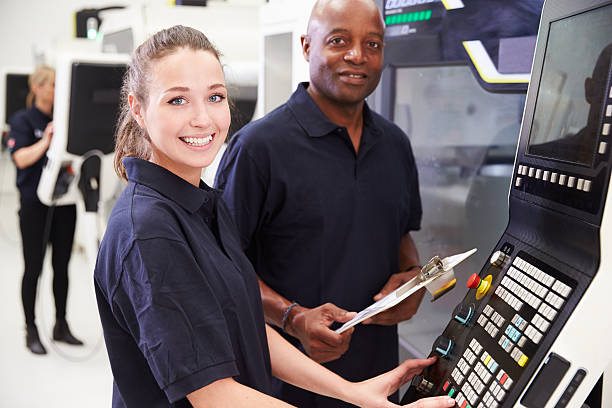 A picture of an engineer training an apprentice. industry 4.0 gives more room for advancement in manufacturing as menial tasks can be assumed by robots.