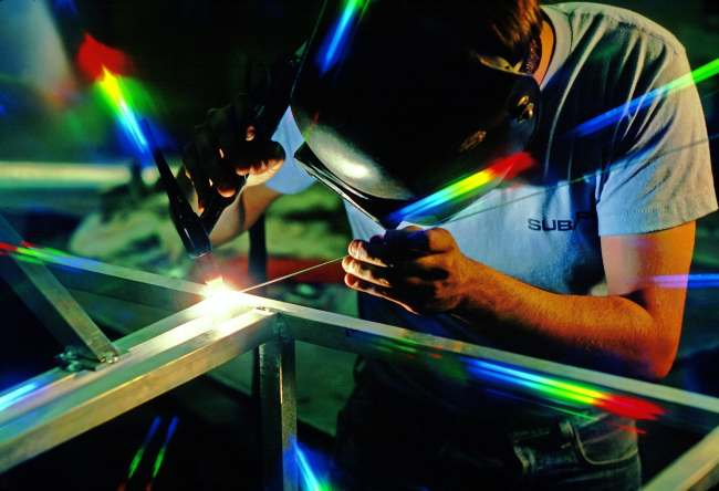 a picture of a welder at work welding part of a steel frame structure