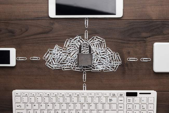 A picture of digital devices on a table connected through a chain of paper clips.